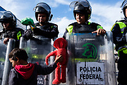 Elias, Honduran child migrant, hands Elmo doll to riot police officer at El Chaparral border crossing near the US-Mexico border in Tijuana, Mexico on November 22nd, 2018. The officers blocked the road due to the protest by the part of Central American migrants to seek asylum in the US.