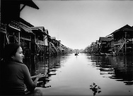 Through the floating village: Woman scans the houses perched high on posts above the flooded main thoroughfare of Kampong Phhluk, which is flooded most of the year by the swollen waters of the Tonle Sap, as she paddles in the waning light of day, Cambodia.