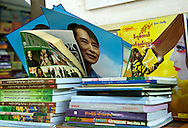 Posters of Aung San Suu Kyi are sold but kept hidden behind piles of book. Yangon, Myanmar. 2012
