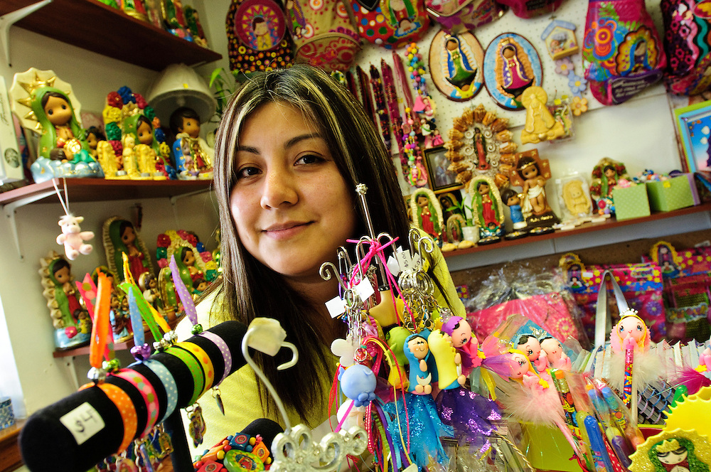 Erika Espinosa and her mother Fidelia Cruz operate Virgencita Plis, a small shop defined by several display counters and racks filled with artwork and items imported from Mexico. The store is one of several dozen located at Azteca Mall in Chicago's Little Village neighborhood, a humble collection of shops spread across two floors of a formerly vacant building. Mall owner Rigoberto Gonzalez is converting his 9 acre lot into a collection of small indoor stores made affordable for local entrepreneurs to operate their own businesses.