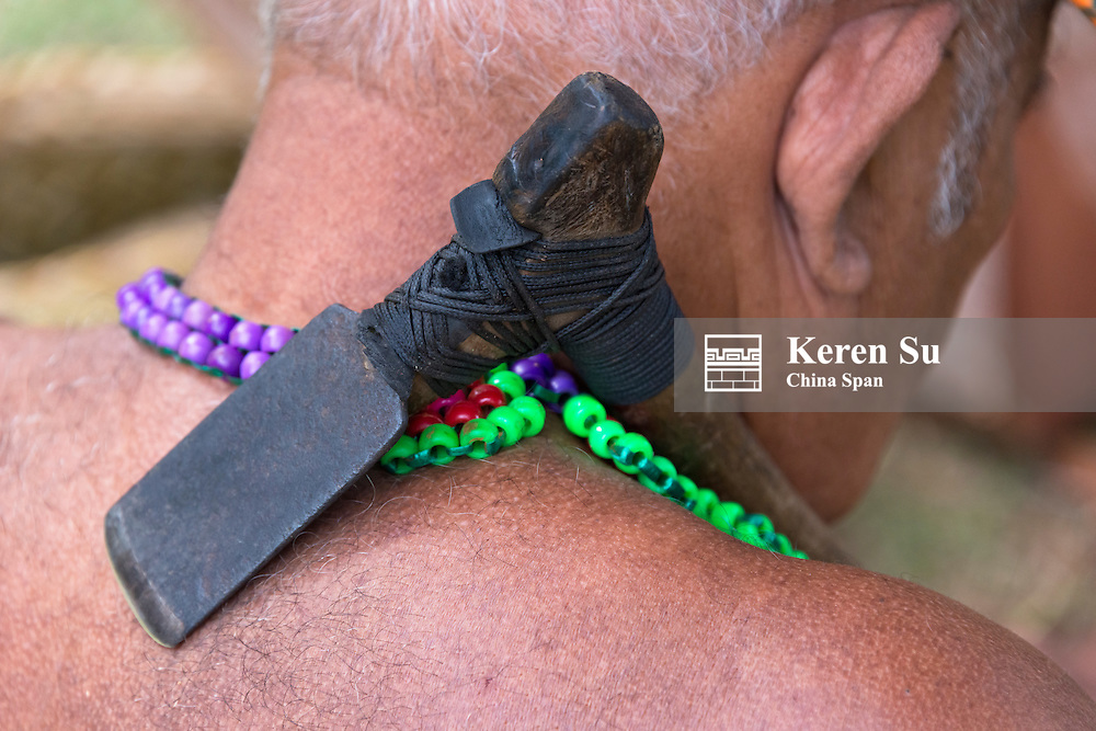 Yapese man carrying carpentry tool, a small ax,  Yap Island, Federated States of Micronesia