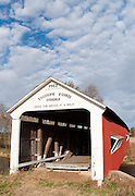 """Thorpe Ford Covered Bridge (163 feet long) was built in Burr Arch style over Big Raccoon Creek in 1912 by J.A. Britton on Catlin Road in Parke County, Indiana, USA. Red and white paint protects the wood. The traditional """"Cross this bridge at a walk"""" sign required slow vehicle speed, but traffic is now diverted to an adjacent modern bridge. Puffy white clouds decorate the blue sky."""