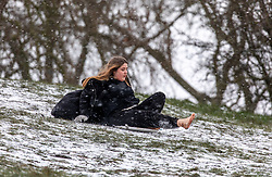 © Licensed to London News Pictures. 09/02/2021. London, UK. Brave. A girl sledges down Primrose Hill barefoot as Storm Darcy hits London and the South East with yet more snow and freezing temperatures today. The Met Office have issue numerous weather warnings for heavy snow and ice with disruption to travel, power cuts and possible stranded vehicles as the bad weather continues throughout the country.  Photo credit: Alex Lentati/LNP