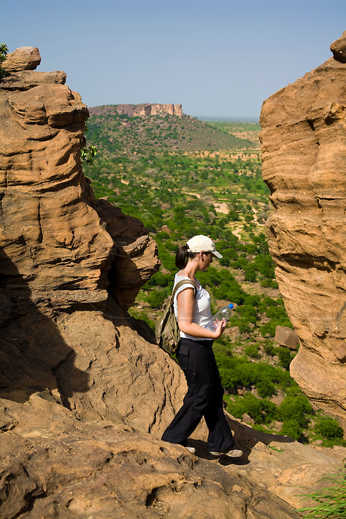 Tourist starts her descend of the cliff near Indelou village. The Dogon Country is the most visited part of Mali with tourists visiting its tipical  villages that can be located on the cliff, on the sandy plain or in the rocky plateau