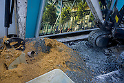 A digger rests with its bucket in construction sand mix next to a illustration of a Leadenhall building in the City of London.