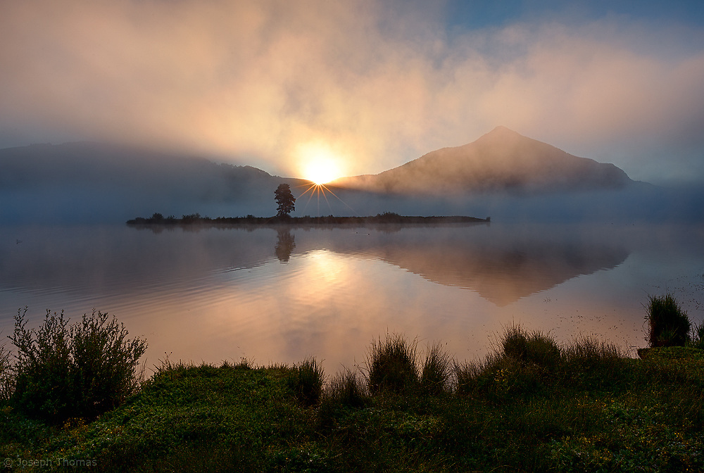 Mount Crested Butte is reflected on a misty lake at sunrise.