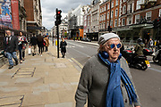 Stylish older man wearing blue glasses, scarf and headphones walks along Piccadilly on 25th May 2021 in London, United Kingdom. As the coronavirus lockdown continues its process of easing restrictions, more and more people are coming to the West End as more businesses open.