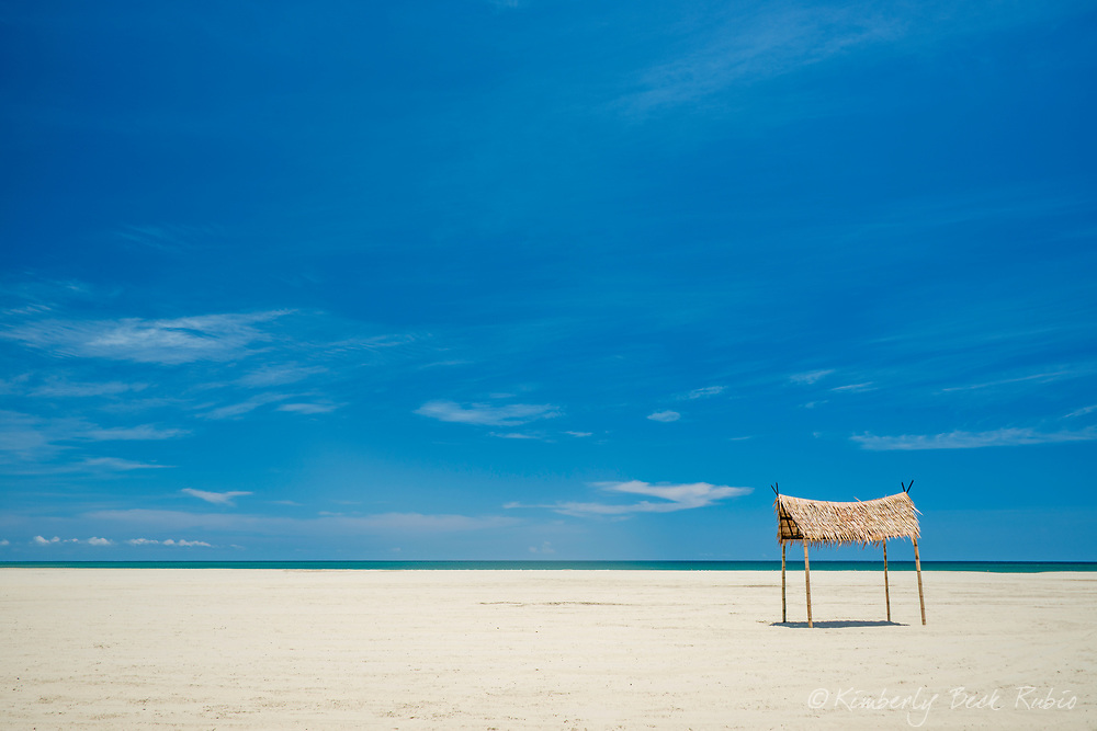 Wide, pristine beach with inviting palapa – a thatched hut – offering shady relief from the 100-degree-heat. Northern coast of Borneo, Sabah State, Malaysia.