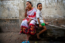 Aging sex worker Josna, 60, left, looks for a customer as her daughter Tanya, 7, sits by at brothel in Faridpur, Bangladesh.<br /> <br /> Deserted by the man who fathered her daughter, she, like many her age, has a difficult time pulling in enough clients to support her family. <br /> Growing old does not mean the end of one's career, but it does mean working harder for a fraction of the pay a younger woman can expect. When Josna can't buy food for Tanya, 7, she has to borrow from the neighbours.