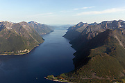 Fjord in Norway surrounded by mountains | Hjørundfjorden med  Leknes i framkant av bildet, etterfulgt av Breidfonnhornet, Blåbreen, Tungremtindane og Hundatinden. Flatnes i venstre bildekant, etterfulgt av Lynghalstinden, Holmshornet, Sylvkallen, Storhornet, Geithornet og Høgenipa. I bakgrunnen skimter du Solavågen.