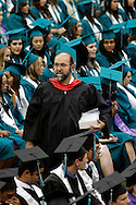 Deer Valley High School teacher Jeff Adkins is surrounded by a sea of caps and gowns as he watches over students before graduation on Friday, June 8, 2012.  (Photo by Kevin Bartram)
