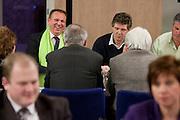 Kandidaat-voorzitter Ton Roerig (groene sjaal) praat met CDA leden. Op de voorgrond rechts praat Ruth Peetoom. De zes kandidaten voor het voorzitterschap van het CDA presenteren zich aan de leden in een zaal in Eindhoven