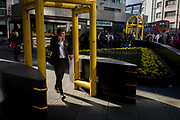 Yellow security gate scanners, still in place the day after Margaret Thatcher's ceremonial funeral at St Paul's Cathedral that required tight security, remains as a backdrop for commuting or waiting Londoners. Beneath the reinforced arch, the commuters text and check messages or attend to children in buggies. Before their imminent removal, they made an incongruous sight in the area as people passed their ugly presence. The high-security event brought much of the City of London to a standstill as arrangements for Thatcher's cortege passed nearby to the cathedral where 2,000 VIPs gathered to honour the former British Prime Minister.
