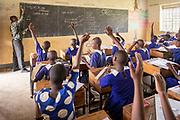 View of school children raising hands to answer teachers questions, The Musoto Christian School, Uganda