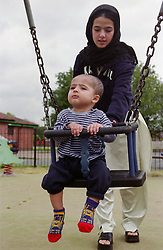 Mother pushing young son on swing in children's playground,
