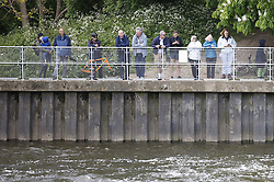 © Licensed to London News Pictures. 10/05/2021. London, UK. People watch as a young minke whale is seen in the River Thames in south west London. Fire crews and the British Divers Marine Life group worked with an Rescue Royal National Lifeboat Institute (RNLI) crew in an effort to save the whale after it got stuck last night. But it is now free . Photo credit: Peter Macdiarmid/LNP