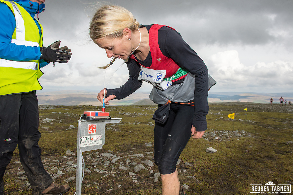 Runners dib in on the summit of Ingleborough in the Yorkshire Dales during the 60th Yorkshire Three Peaks Race.