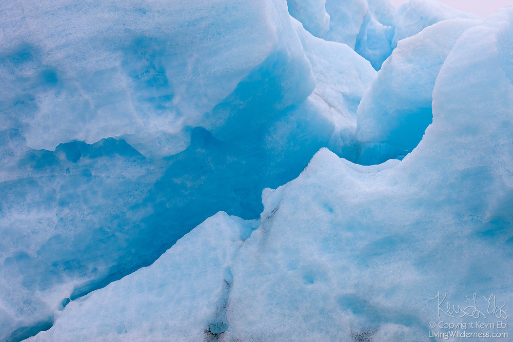 A crack is visible in a large, blue iceberg in glacial lagoon of Jökulsárlón in southern Iceland. The glacial lake is full of icebergs that have fallen from the Breiðamerkurjökull glacier.