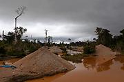 Deforested landscape and gravel mounds to mount ramps for the separation of gold sediments in San Jose de Kareme, Peru.