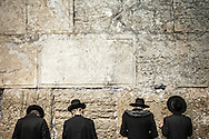 """Ultra-orthodox jews praying at the Western Wall. The sages state that anyone who prays in the Temple in Jerusalem, """"it is as if he has prayed before the throne of glory because the gate of heaven is situated there and it is open to hear prayer"""""""