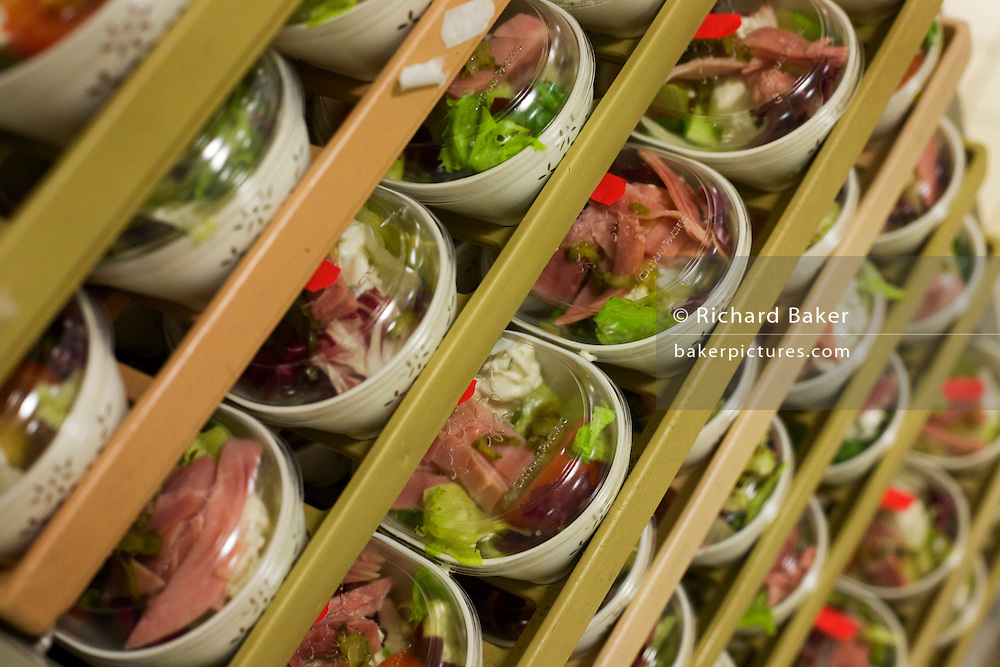 """Meat salads are stacked in readiness for an airline flight in the world's largest independent provider of airline catering and provisioning services, Gate Gourmet, on the southern perimeter road at Heathrow Airport, West London. Gate Gourmet serve more than 200 million meals on 2 million airline flights a year to their 250-plus airline customers at more than 100 airport locations around the globe. Apart from creating the bespoke meals for an airline's culture and ethnic demands, that pack the pre-flight carts, deliver and load into the aircraft galleys and afterwards, they dispose of the waste and strip, wash and sterilize the equipment. From writer Alain de Botton's book project """"A Week at the Airport: A Heathrow Diary"""" (2009). ."""
