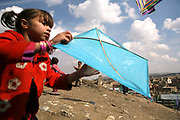Sobra, 6 or 7, with her own kite, along with other Noor Agha's children, flies the kites next to their house in the middle of a cemetery, Kabul, Afghanistan, Saturday, March, 10, 2007. Noor Agha is a renowned kite maker who made kites for the movie makers of the best-selling novel, The Kite Runner, which will be distributed by Dreamworks and Paramount Vantage in Nov. this year. Noor Agha's wives, using their special glue, help him produce enough kites to please the clients' needs. Some of his children can also make their own kites with plastic bags and bamboo sticks. As the Afghan New Year's Day (Nawruz) approaching on March 21, the finger tips of Noor Agha's family got busier for mass production.