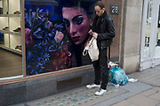 Photograph of a woman's head with staring eyes makes an interesting street scene as a man interacts unbeknown while texting on his mobile phone. New Bond Street, London, UK. A weird visual juxtaposition is created as people integrate with the large scale window display.