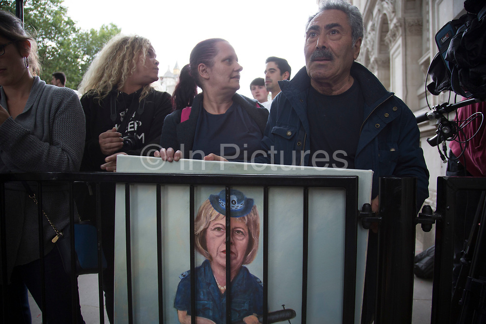 Political artist Kaya Mar with his latest painting behind bars on the day that the new Conservative Party leader Theresa May MP became Prime Minister of the UK, as protesters and public gathered outside Downing Street on 13th July 2016 in London, United Kingdom. This painting portrays Theresa May as a thuggish police woman holding a truncheon with a nail through it. Political satire on her hardline dealings with the police force. photo by /In Pictures via Getty Images