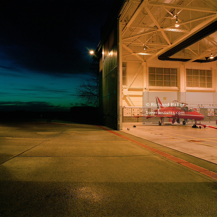 A red Hawk jet aircraft belonging to the elite 'Red Arrows', Britain's prestigious Royal Air Force aerobatic team, is parked in the hangar at RAF Scampton, Lincolnshire, the home base for the squadron. Night is falling with only blue daylight remaining in the western sky and the warm light from the hangar spills out of the giant open doors on to the concrete. The aircraft awaits attention from the engineer's night-shift who service and maintain all 11 of the famous red aerobatic jets before flying the next morning. The hangaran original World War 2 shelter for the Lancaster bombers of 617 Dambusters squadron who attacked the damns of the German Ruhr valley on 16th May 1943 using the Bouncing Bomb. The Red Arrows use this and nearby offices administrative nerve-centre for the 90-plus displays they perform a year. .
