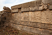 Tzompantli or Skull Platform in Chichen Itza. Displayed skeletonized warriors with arrows and shields snakes and serpents. Also on this wall is Kukulcan, the serpent sculpture.