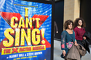 Two women walk past a poster for the X Factor EWest End musical I Can't Sing. The show was written by Harry Hill and Steve Brown and is a send up of the popular TV show talent conpetition. London, England, UK.