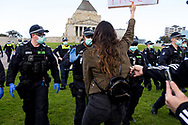 MELBOURNE, VIC - SEPTEMBER 05: A woman stands against police during the Anti-Lockdown Protest on September 05, 2020 in Sydney, Australia. Stage 4 restrictions are in place from 6pm on Sunday 2 August for metropolitan Melbourne. This includes a curfew from 8pm to 5am every evening. During this time people are only allowed to leave their house for work, and essential health, care or safety reasons. (Photo by Dave Hewison/Speed Media)