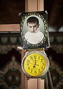 """Picture of a child and clock hanged in Yodgar's house (a """"Khalifa"""", spiritual leader) in the Langar village, in the Wakhan Corridor, Tajikistan side, in the Pamir mountains. Afghanistan is on the other side of the Panj river.<br /> <br /> Tajikistan, a mountainous landlocked country in Central Asia. Afghanistan borders it to the south, Uzbekistan to the west, Kyrgyzstan to the north, and People's Republic of China to the east. Tajikistan also lies adjacent to Pakistan separated by the narrow Wakhan Corridor.<br /> Tajikistan became a republic of the Soviet Union in the 20th century, known as the Tajik Soviet Socialist Republic.<br /> It was the first of the Central Asian republic to gain independence in December 1991."""