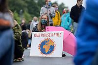 "25 SEP 2020, BERLIN/GERMANY:<br /> Junge Frau mit Schild ""Our House is on Fire"", Fridays for Future Demonstration fuer Massnahmen gegen den Klimawandel, Brandenburger Tor, Strasse des 17. Juni<br /> IMAGE: 20200925-01-045<br /> KEYWORDS: Protest, Demonstrant, Demonstranten, Demonstratin, Schueler, Schüler, Klimakatastrophe, FFF, Mundschutz, Mund-Nase-Schutz, Abstand"