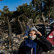 MORIA, GREECE - SEPTEMBER 10: An Afghan asylum-seeker retrieves her family's belongings from their burnt out tents as fires which started Tuesday night continue to rage into Thursday morning inside of Moria camp on September 10, 2020 in Moria. According to UNHCR, current numbers say the asylum-seekers displaced from the encampment are around 12,000. (Photo by Byron Smith/Getty Images)