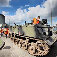 Nederland, Amsterdam , 27 april 2012..Vrijdag 27 april zetten de stakende medewerkers van de eiwitfabriek van Cargill in Amsterdam zwaar geschut in bij hun strijd tegen ontslag. Om hun eisen kracht bij te zetten, zetten zij om 09.00 uur een twintig ton wegende militaire tank compleet met vlammenwerpers voor de deur bij het Amsterdamse hoofdkantoor...De stakers zijn boos omdat er onvoldoende schot zit in de onderhandelingen over een sociaal plan. Volgens FNV Bondgenoten zijn er meer dan voldoende vacatures binnen het concern om te voorkomen dat er medewerkers op straat komen te staan. Vakbondsbestuurder Erik de Vries: ?Het is te gek voor woorden dat je hier na een week staken met een tank voor moet rijden als je afspraken wilt maken. Als Cargill een sociaal bedrijf is, dan zegt het vandaag toe dat deze mensen hun baan houden.?..Het rommelt al langer bij Cargill. Op meerdere plaatsen in het land vinden momenteel reorganisaties plaats, waarbij geruisloos medewerkers worden ontslagen. ?In Bergen op Zoom bijvoorbeeld horen medewerkers ?s ochtends dat ze ?s middags geen werk meer hebben?, aldus De Vries. ?Ze krijgen een zakje geld mee en worden onmiddellijk naar huis gestuurd. Dat gaan we hier niet laten gebeuren. Collega?s van meerdere locaties in Nederland hebben toegezegd vrijdag naar Amsterdam te komen.?..Het is geen toeval dat juist vandaag medewerkers hun boosheid uiten. Volgens bronnen krijgt de locatie vandaag hoog bezoek van het hoofdkwartier uit Amerika, om een omgebouwde fabriek te inspecteren. ?We gaan deze heren vanmiddag heel duidelijk maken dat we hier geen Amerikaanse toestanden willen?, aldus FNV Bondgenoten..Foto:Jean-Pierre Jans