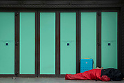An anonymous homeless person lies on the ground next to a suitcase in a red sleeping bag, in the doorway of the former high street retailer, Top Shop at Oxford Circus in the West End, on 8th July 2021, in London, England.