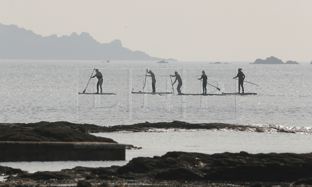 © Licensed to London News Pictures. 29/03/2019. Marazion, UK. Paddleboarders enjoy the warm weather conditions on the coast at Marazion in Cornwall, West England. Photo credit: Jason Bryant/LNP