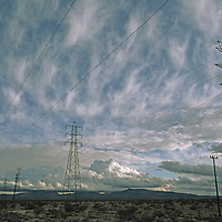 Electric transmission lines are contrasted against high clouds.