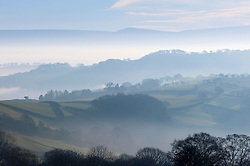 © Licensed to London News Pictures. 19/01/2016. Powys, Wales, UK. A view just after sunrise looking, over Mid Wales hills shrouded in mist, towards Hay Bluff and The Black Mountains in the distance. Photo credit: Graham M. Lawrence/LNP