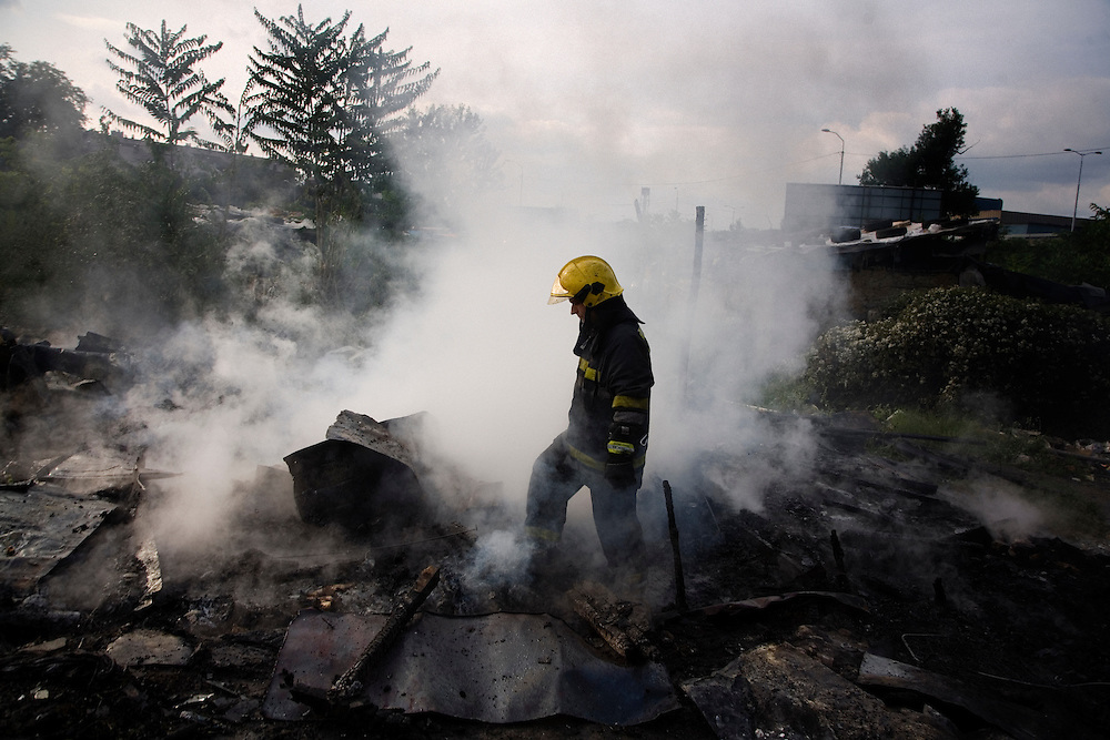 Firefighters battle a house fire on the day before relocation. The suspected arson happened in an abandoned home in a remote part of the camp.