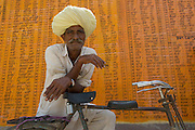 A village man stands before a wall painted with the names of people in his village who have received work from the Government. Each villager is optioned 100 days of work per year. - Hindoli, India