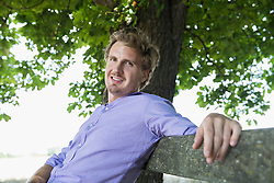 Portrait of mid adult man sitting on bench, smiling