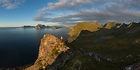 Female hiker on summit of Hornet with panoramic view over Myrland, Flakstadøy, Lofoten Islands, Norway