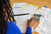 A young lady sits at her kitchen table at home checking over the household bills.  he rising costs of all the household bills. Dealing with debt. Household utility bills making it difficult for a British<br /> home owner to afford. Difficulty paying gas and electricity bills is common<br /> as the economic downturn makes personal finances feel the pinch. London, UK.