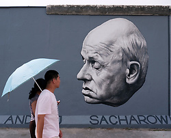 Chinese tourists walk  in front of painting of Andrei Sakharov by artist Dmitry Vrubel newly repainted on Berlin wall at East Side Gallery in Berlin August 2009