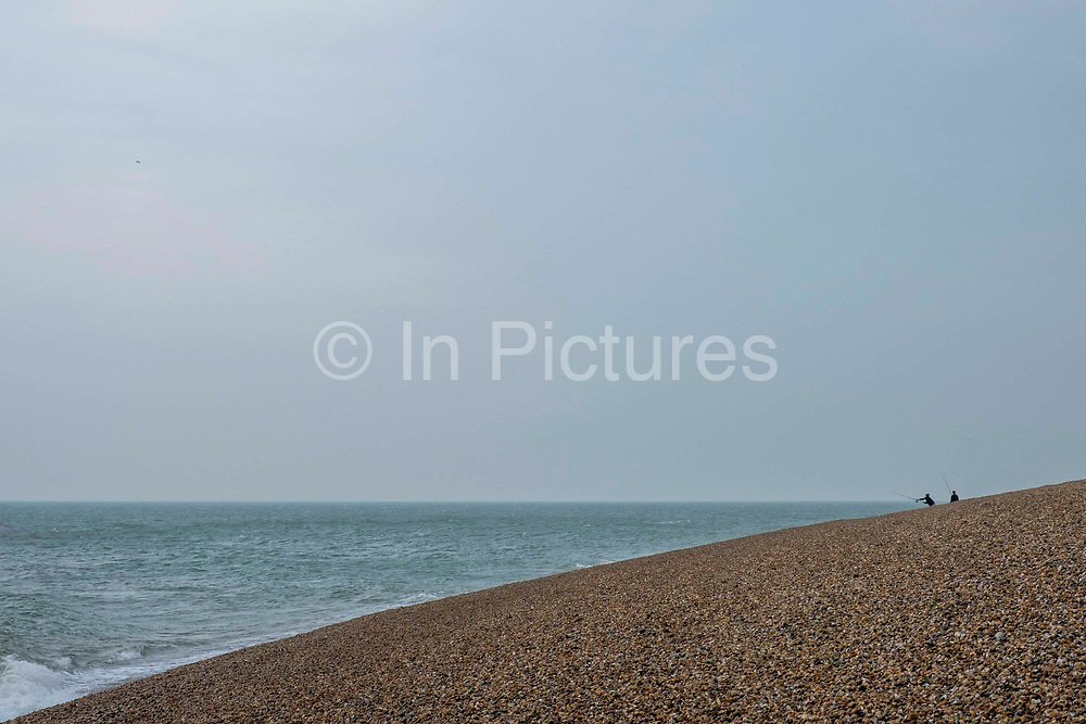 Two people fishing on Folkestone seafront looking out across Hythe Bay toward Dungeness Power station on the 12th of June 2020, Folkestone, United Kingdom.