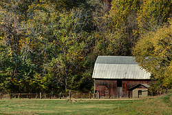 2015 Oct 20:  a rustic frame barn with hay loft stands behind the well house on a farm in the fall in Parke County Indiana.<br /> <br /> This image was produced in part utilizing High Dynamic Range (HDR) processes.  It should not be used editorially without being listed as an illustration or with a disclaimer.  It may or may not be an accurate representation of the scene as originally photographed and the finished image is the creation of the photographer.