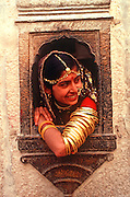 INDIA, PORTRAITS Portrait of a Rajasthani woman in the carved window of home in Jaisalmer