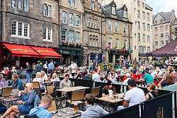Edinburgh, Scotland, UK. 17th August  2021.  News that supply chain problems might cause a shortage of beer in Scotland did not deter many visitors to Edinburgh Old town who enjoyed  a warm afternoon in sunshine at one of the many outdoor bars in the city. Pic; Beer gardens in Grassmarket were very busy. Iain Masterton/Alamy Live news.